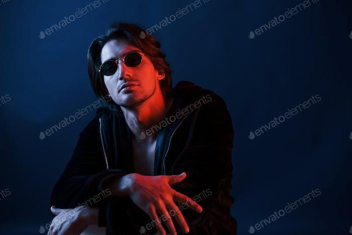 Schöner Mann mit Brille und schwarzer Kleidung ist im Studio mit blauer Neonbeleuchtung