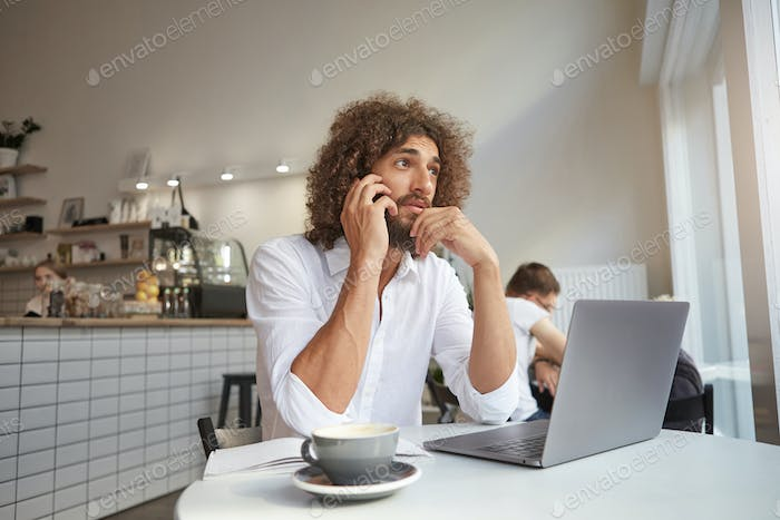Indoor shot of handsome pretty young man working remotely in public place, talking on phone