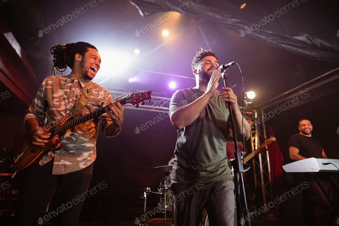 Cheerful guitarist with singer performing on stage at nightclub