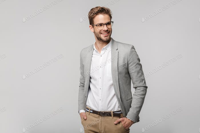 Portrait of happy young businessman posing at camera and smiling