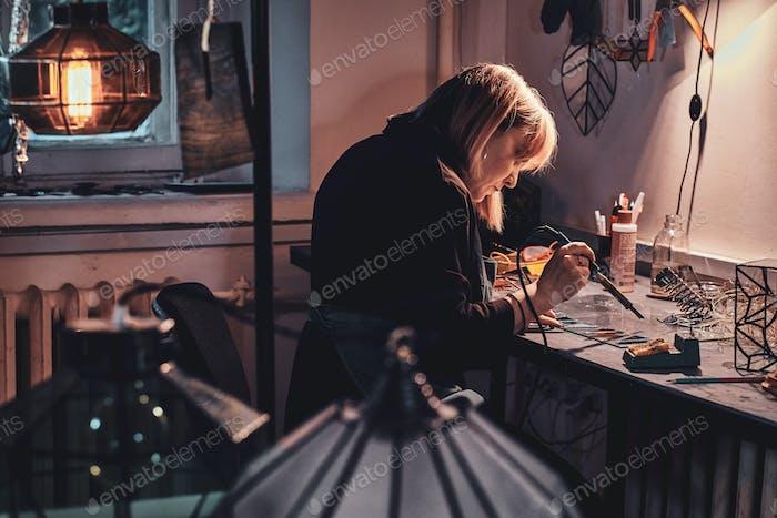 Frau arbeitet an ihrem Lampenprojekt im Lampenstudio.