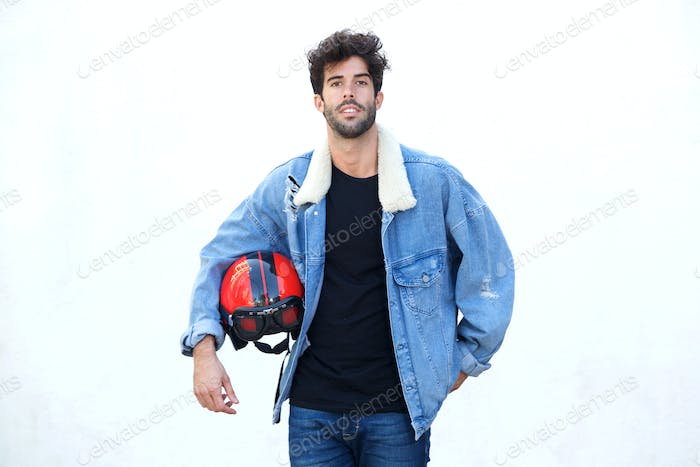 Serious motorcyclist wearing jean jacket and holding helmet