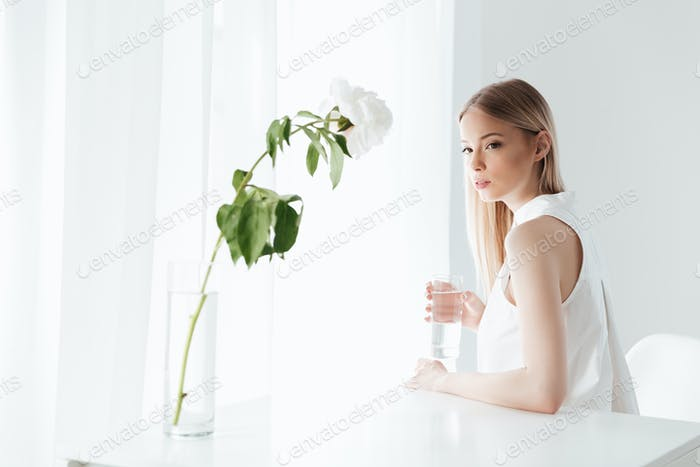 Serious blonde lady sitting indoors near flowers