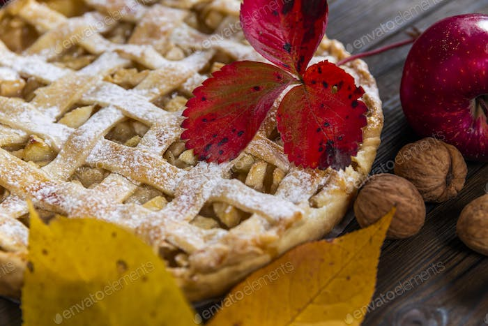 Homemade American Apple Pie Decorated with fresh apples and autumn leaves