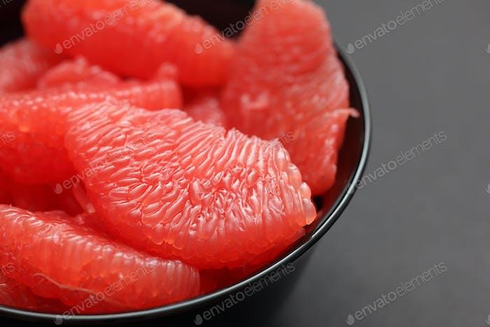 Pomelo rojo en un tazón negro