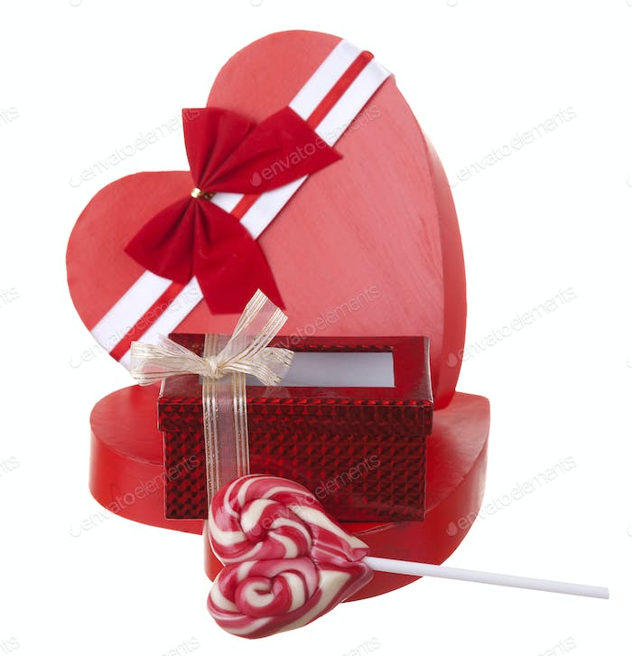 Red box in heart shape with a lollypop isolated on white backgro