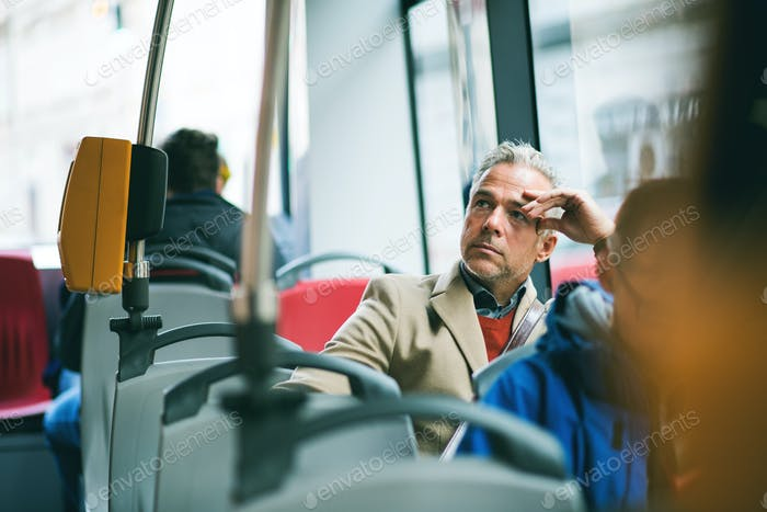 Tired mature businessman travelling by bus in city.
