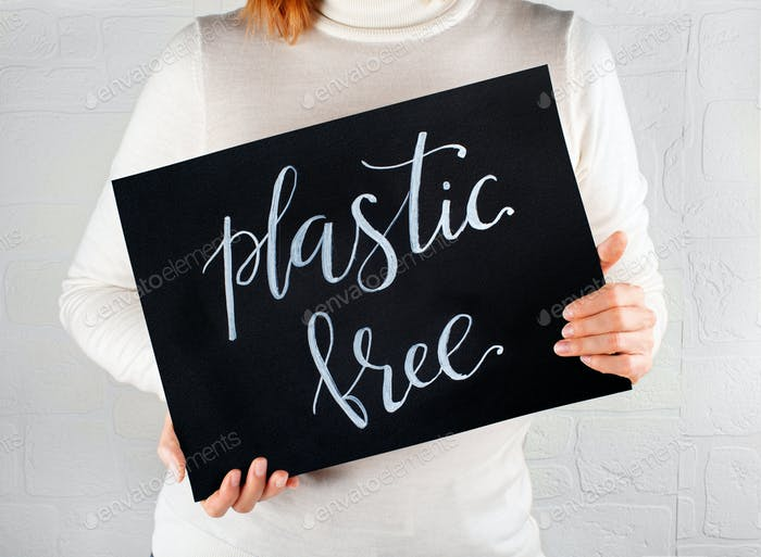 Woman keeping a small chalkboard with Plastic Free lettering