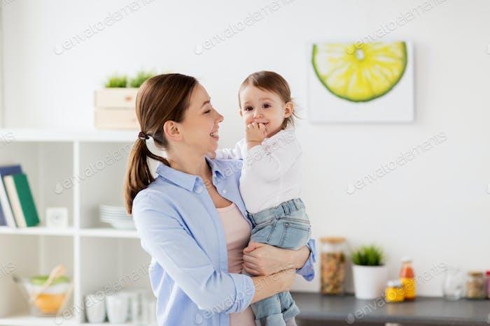 mère heureuse et petite fille bébé à la maison cuisine