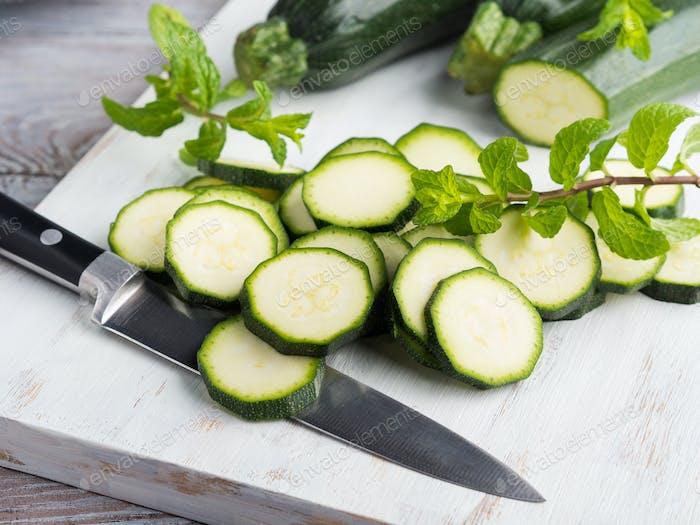 Schneiden von Zucchini auf Holzbrett