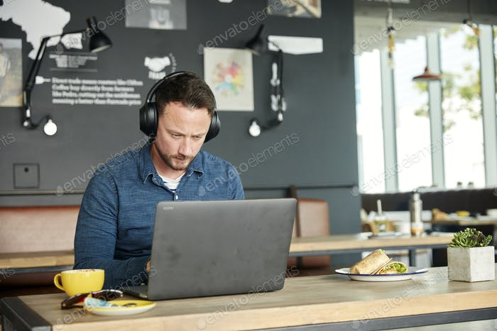 Man seated in a cafe, working on a laptop
