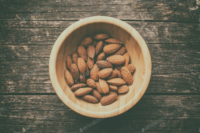 Dried almonds in wooden bowl.