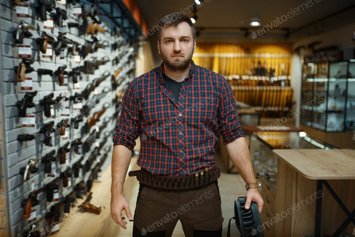 Man in hunting uniform holds ammo belt in gun shop