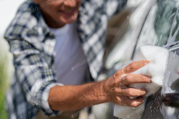 Closeup of man hand washing car
