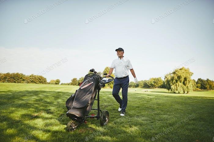Lächelnder Senior Mann schiebt seine Schläger auf einem Golfplatz