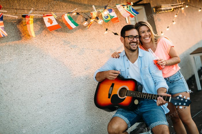 Young man playing guitar for friends and his girlfriend