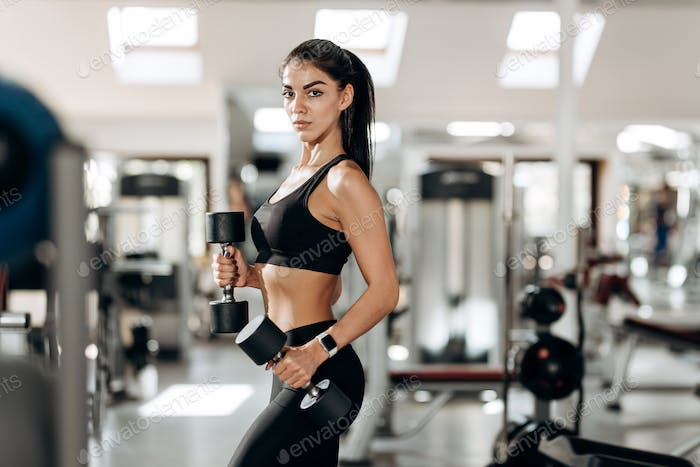 Athletic girl dressed in black sports top and tights builds up muscles with dumbbells in the gym