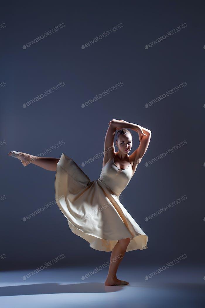 Junge schöne Tänzerin in beige Kleid tanzen auf grauen Hintergrund