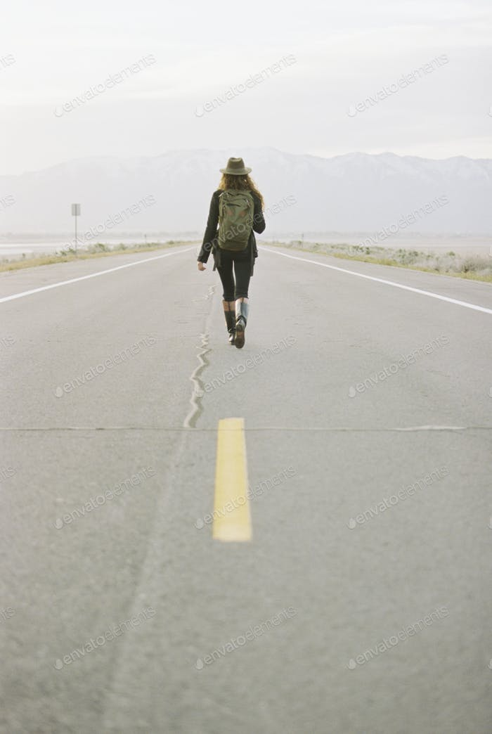 A woman carrying a backpack walking down the centre line of a  country road.