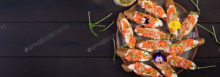 Salmon sandwiches with cream cheese and microgreen on wooden tab