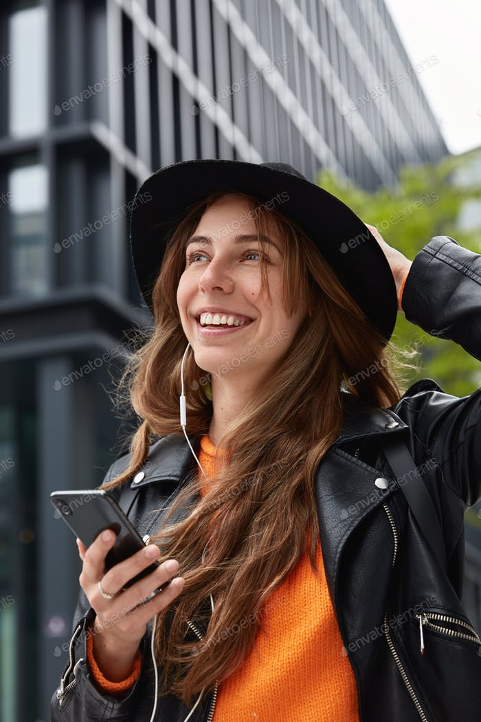 Attractive hipster girl enjoys listening music or audio book on cellular, installs app for creating