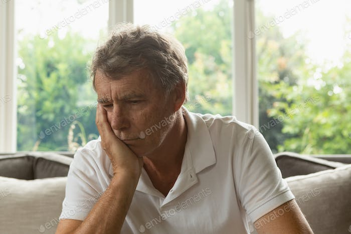 Sad active senior Caucasian man with hand on face sitting on sofa in a comfortable home