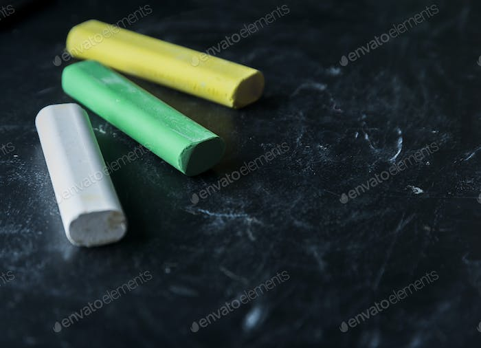 Black old empty chalkboard for copy space with colorful pieces of chalk. Blackboard with chalks