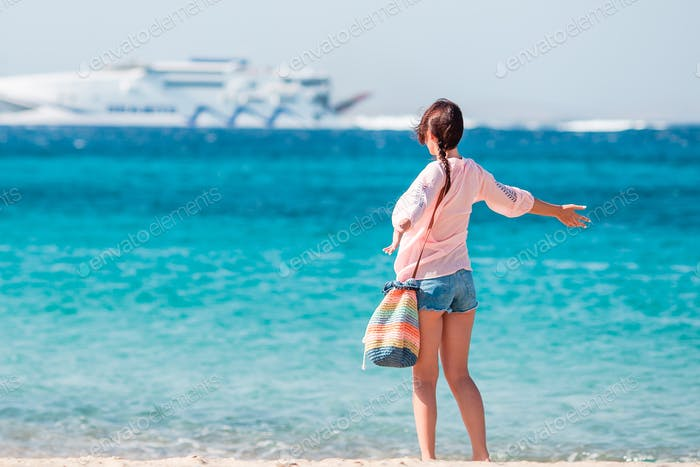 Young girl on the beach background big cruise liner. Woman enjoy her wekeend on one of the beautiful