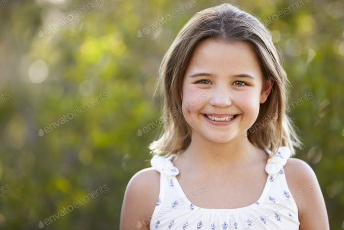 Portrait of smiling young girl looking to camera outdoors