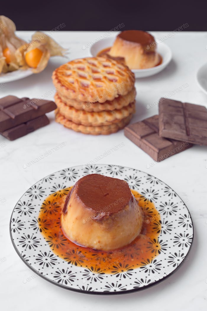 homemade flan cookies and chocolate on marble illuminated with natural light