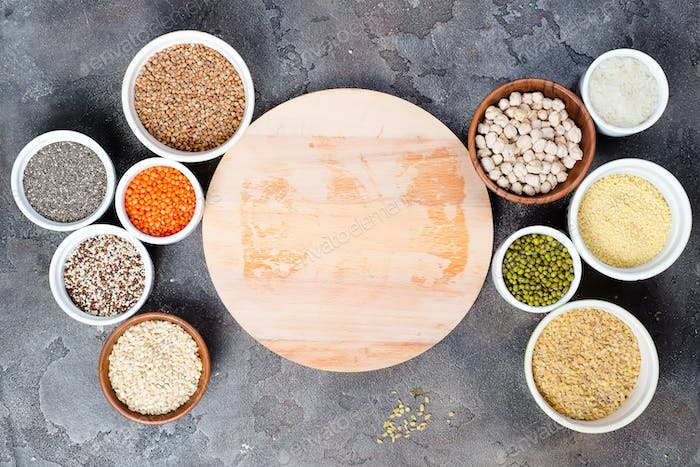 Superfoods and cereals selection in bowls with wooden board for your text