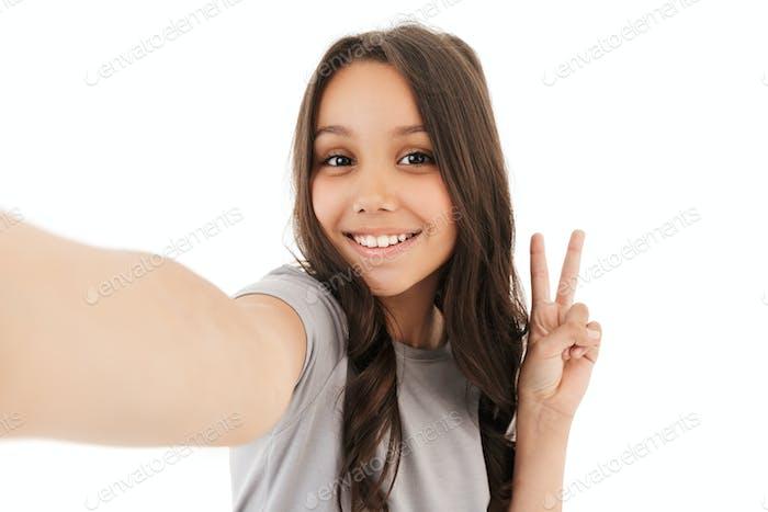 Pretty cute girl make selfie looking camera showing peace gesture.