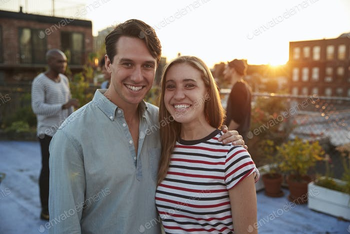 Young white couple embracing at a rooftop party