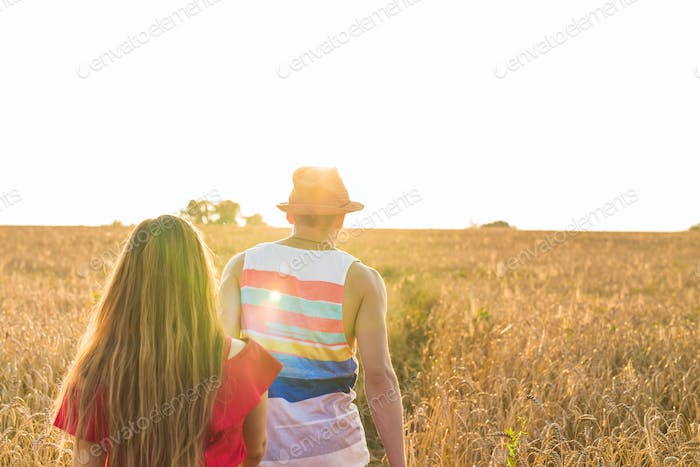 Young love couple walking on field in sunlight