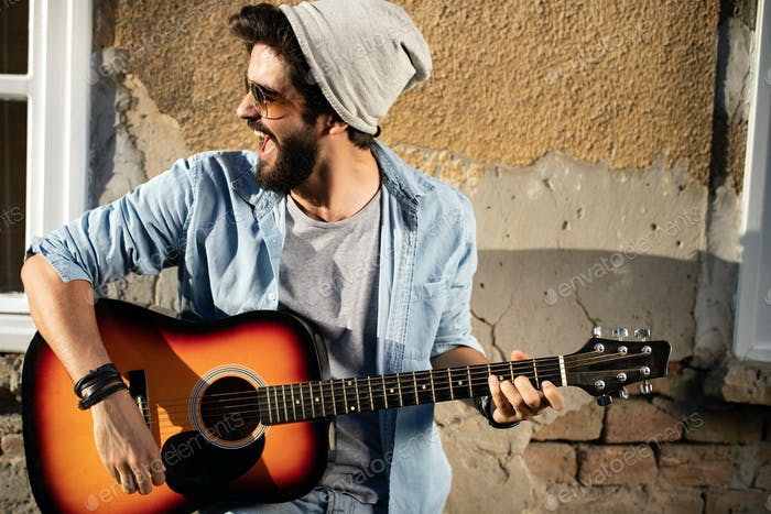 Young musician handsome man with guitar in city