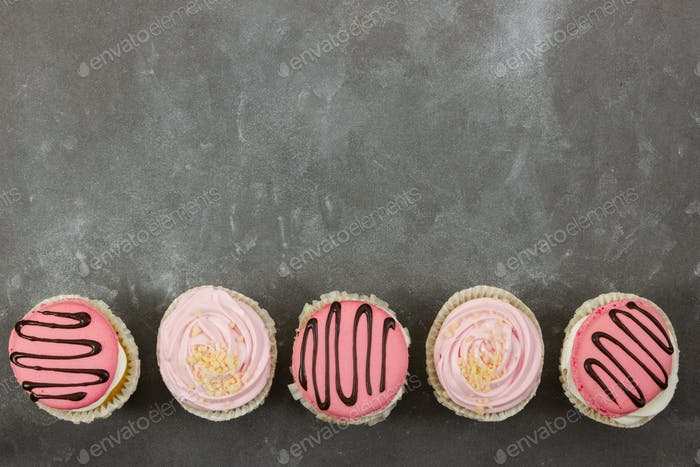 Strawberry cupcakes on gray stone background.