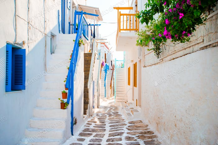 The narrow streets of greek island with blue balconies, stairs and flowers. Beautiful architecture