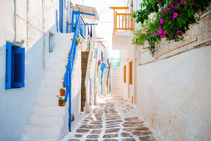 Die engen Gassen der griechischen Insel mit blauen Balkonen, Treppen und Blumen. Schöne Architektur