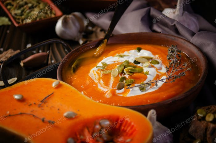 Clay dish with homemade rustic pumpkin soup with seeds on wooden table with bread and greens aside