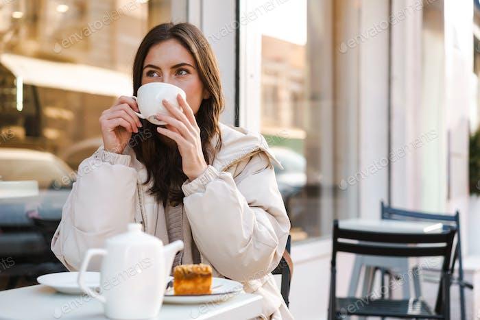 Fröhliche junge Frau beim Tee mit Kuchen