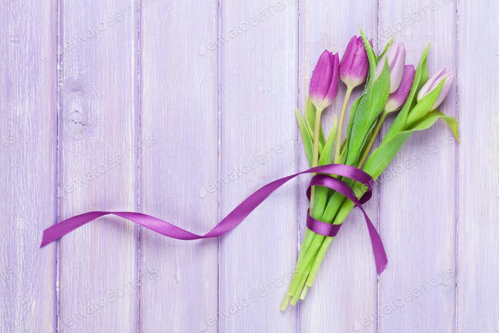 Purple tulips on wooden table
