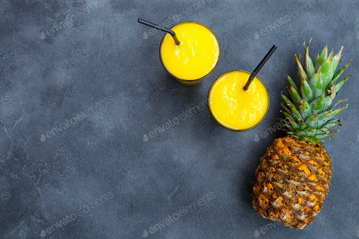 Pineapple with Tropical Fruit Juice, Smoothie on Dark Background. Copy Space. Top View.