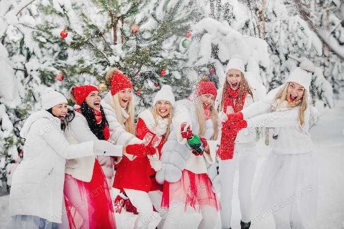 A lot of girls open a bottle of champagne violently in the winter new year's forest.Girls in red