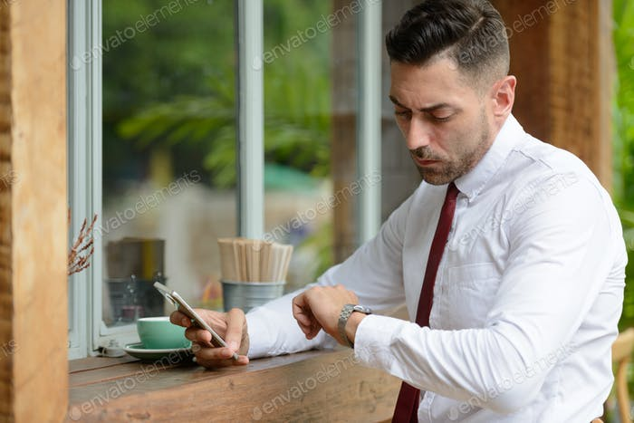Portrait of businessman waiting and checking time at the coffee shop