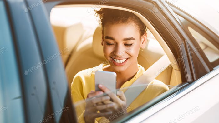 African-Americam Woman Texting On Phone In Car