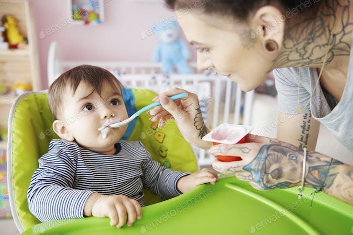 Mumie Fütterung Junge mit Joghurt