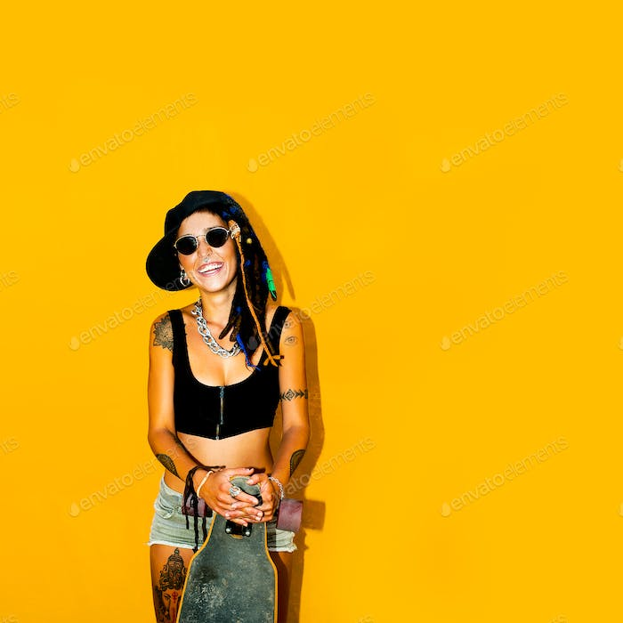 Fashion Rasta girl with dreadlocks and tattoos. Skateboard Stree