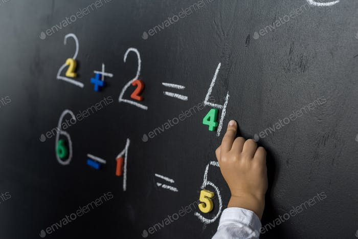 cropped shot of child studying numbers on chalkboard