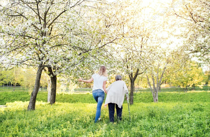 Elderly grandmother with crutch and granddaughter in spring nature.