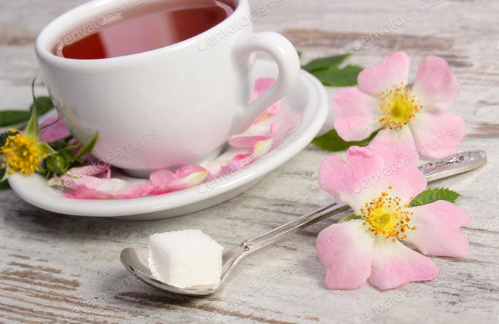 Cup of tea and wild rose flower on rustic wooden background